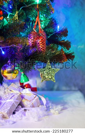Christmas fir tree with red and gold decoration,shiny blue and green lights and presents boxes - vertical background - stock photo