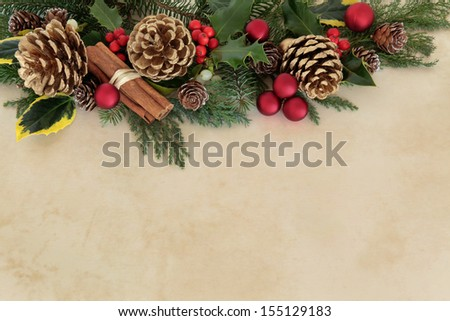 Christmas floral background border with red baubles, holly, mistletoe and cinnamon spice with gold pine cones over parchment.  - stock photo