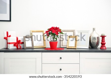 Christmas flower poinsettia and decorations on drawers with Christmas decorations, on light background - stock photo