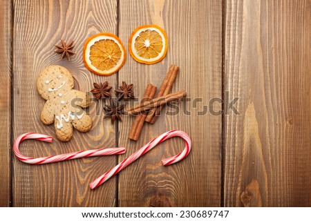 Christmas food decoration with gingerbread cookies, spices and candies. View from above on wooden background with copy space - stock photo