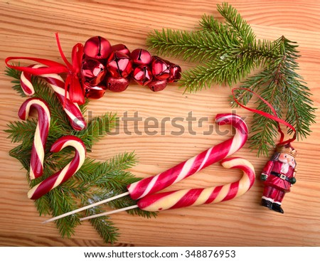 Christmas frame from Christmas candy canes, red bolls,  toy Santa and green tree twigs - stock photo