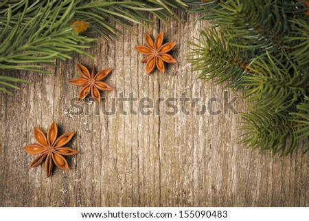 Christmas frame (spruce branches and star anise) on the old wooden background, horizontal - stock photo