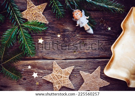 Christmas frame: white angel, golden stars and evergreen branches on old wood. - stock photo