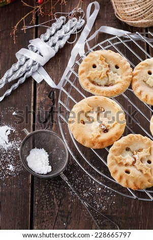Christmas fruit mince pies on a cooling rack and decorations over rustic wooden background. Selective focus - stock photo