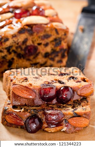 Christmas fruitcake slices garnished with cherries almonds and brazil nuts on chopping board. - stock photo