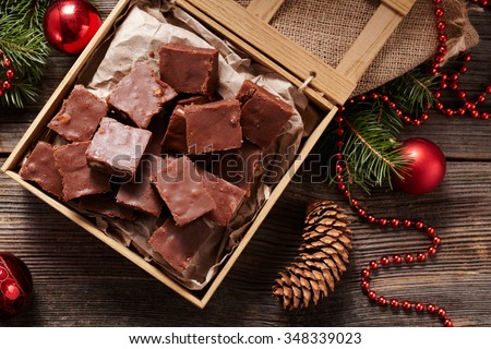 Christmas fudge traditional homemade chocolate sweet dessert food in wooden box on vintage table background. Top view. Delicious unhealthy treat. - stock photo