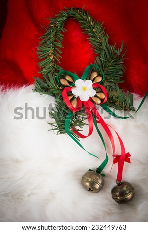 Christmas garland and small bells on red and white fur with dark vignette - stock photo