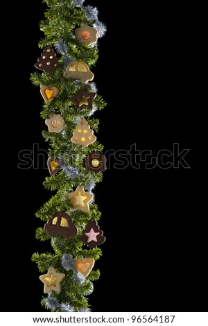 Christmas garland in vertical position with biscuits and candies - stock photo