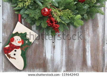 Christmas garland with a snowman stocking on a rustic wooden background. - stock photo