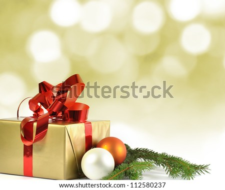 Christmas gift and baubles and bokeh in background - stock photo