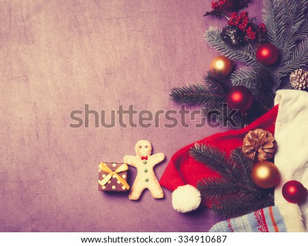Christmas gift and gingerbread man on violet background - stock photo