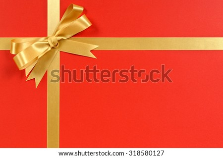 Christmas gift border frame, gold ribbon and bow, red background  - stock photo