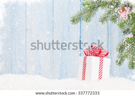 Christmas gift box and fir tree branch in snow. View with copy space - stock photo