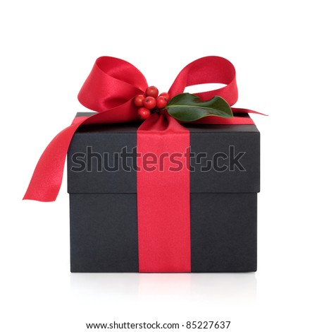 Christmas gift box  decorated with red satin ribbon and bow with holly leaf and berry sprig isolated over white background. - stock photo