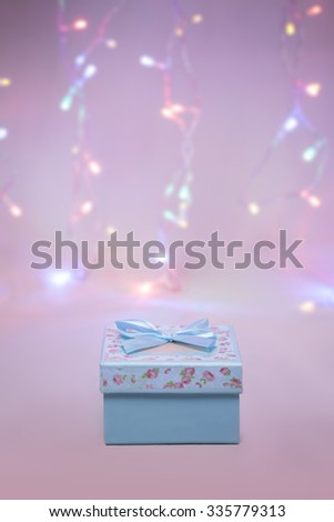 Christmas gift box on soft festive background with lights. Low aperture shot, focus on bow - stock photo