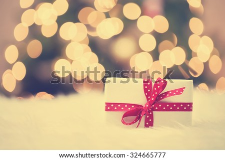 Christmas gift box on white carpet in front of tree - stock photo