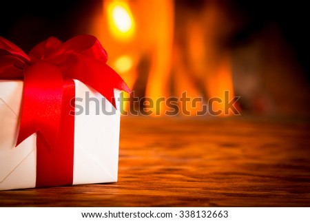 Christmas gift box on wood table against fireplace. Winter holiday concept - stock photo