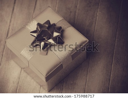 Christmas gift box on wooden table. Photo in old color image style. - stock photo