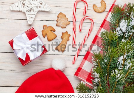 Christmas gift box, santa hat, gingerbread cookies and snow fir tree. View from above over white wooden table background - stock photo