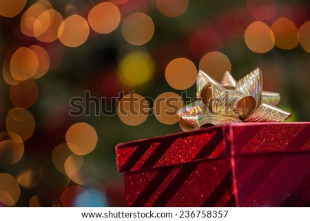 Christmas gift box under a tree with defocused lights and copy space - stock photo