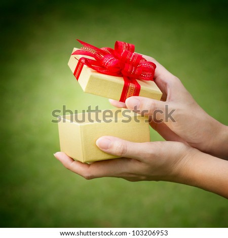 christmas gift box with hand open - stock photo