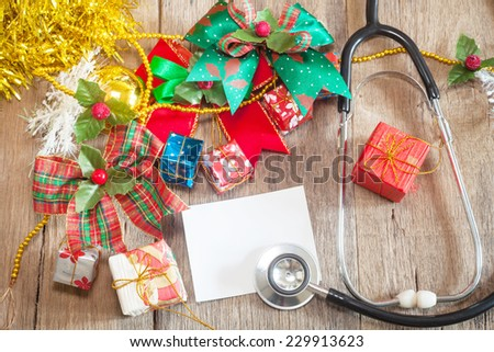 Christmas gift boxes and Stethoscope on wooden background - stock photo