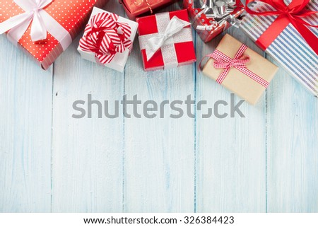 Christmas gift boxes on wooden table with snow. Top view with copy space - stock photo