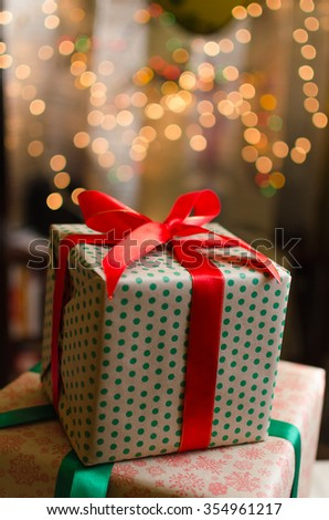 christmas gift boxes wrapped in themed craft paper and satin red bow defocused christmas lights background space for copy text - stock photo