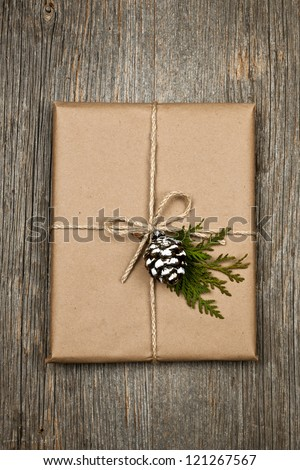 Christmas gift in brown wrapping and string with pine cone decoration on old wood background - stock photo