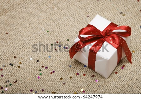 Christmas gift on canvas bacvkground. - stock photo