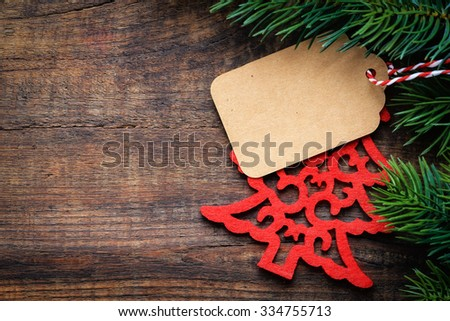 Christmas gift tag with festive felt decoration and pine branches on wooden background with copy space for your text - stock photo