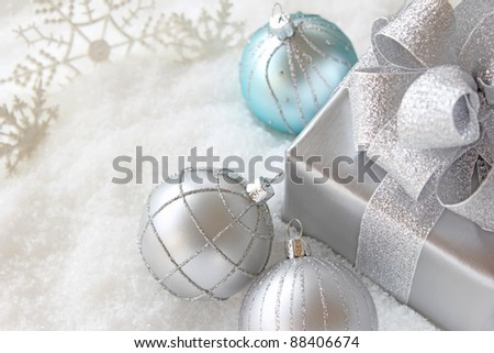 Christmas gift with balls in snow - stock photo