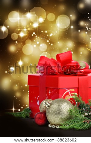Christmas gift with baubles, fir tree branches and sparkling bokeh lights in background - stock photo