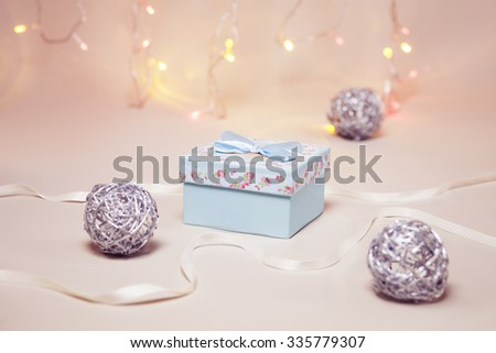 Christmas gift with decorations on festive background with garland lights - stock photo