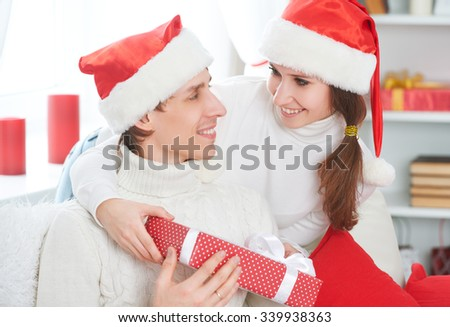 Christmas gift. woman gives a man a surprise gift present box  - stock photo