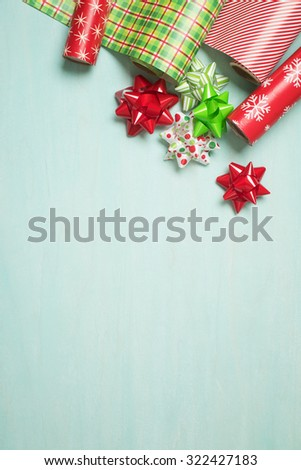 Christmas Gift Wrapping Party Time with Red and Green Colorful Paper and Ribbon Bows on Cyan Blue Shabby Chic Wood Board Background with Room or Space for copy, text, your Holiday Greeting words.   - stock photo