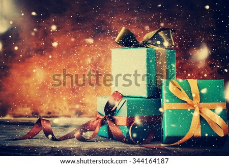 Christmas Gifts. Festive Boxes in Blue Paper with Different Color Bows on Wooden Background. Toned and Drawn Snow - stock photo