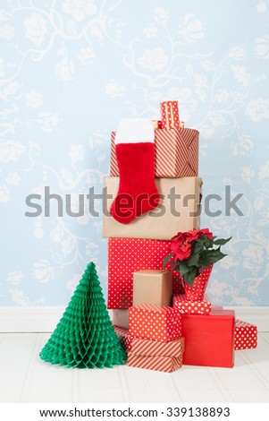 Christmas gifts in interior with blue wall paper - stock photo