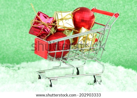 Christmas gifts in shopping trolley, on green shiny background - stock photo