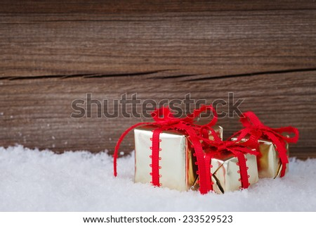 christmas gifts in snow before wooden board - stock photo