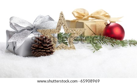 Christmas Gifts lying in snow under a christmas tree - stock photo
