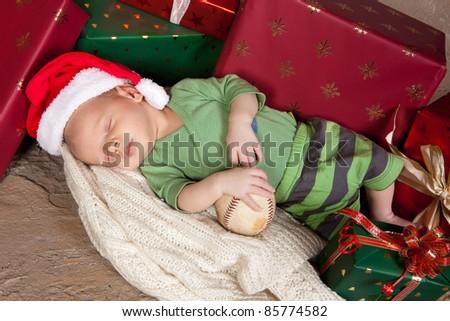 Christmas gifts surrounding a little newborn baby - stock photo