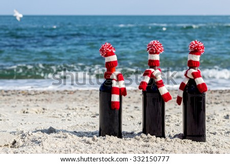 Christmas gifts. Three bottles of wine in knitted hats and scarves on the beach. Selective focus. - stock photo
