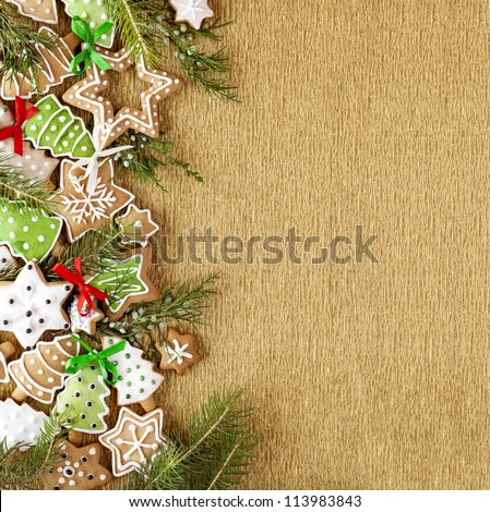 Christmas Ginger and Honey colorful cookies with fir tree branches and bows on the gold wrapping paper background. - stock photo