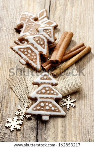 Christmas gingerbread cookies in christmas tree shape on rustic wooden table. Xmas cozy mood, festive atmosphere. - stock photo