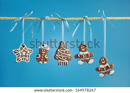 Christmas gingerbread cookies of various shapes hanging on a ribbon on a blue background. - stock photo