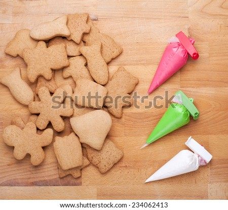 Christmas gingerbread cookies (rabbit, mushroom, snowflake, Christmas tree, fish, bear, man) on a wooden board and cornets with multicolored glaze for painting - stock photo
