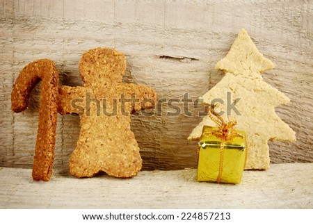 Christmas gingerbread cookies santa claus with gift under christmas tree on wooden surface - stock photo