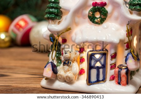 Christmas gingerbread house, close-up next to the Christmas balls with fir branches on a wooden background - stock photo