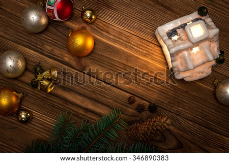 Christmas gingerbread house, next to the tree branches and Christmas balls, and fir cones on the background of the tree view from the top with space for text - stock photo